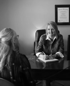 Michelle meeting with a client in her office smiling and taking notes.